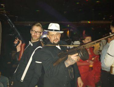 Zwei Männer mit Gewehr im Partyraum